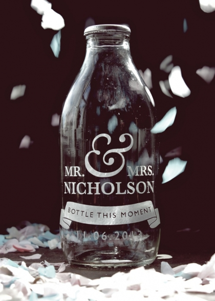 lifestyle image of Personalised Wedding Gift Milk Bottle - Bottle This Moment with white confetti and black wall background