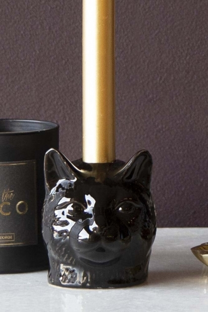 Lifestyle image of the Black Cat Candle Holder with a candle in it and Rockett St George Scented Candles - After The Disco in background on marble console table and dark wall background