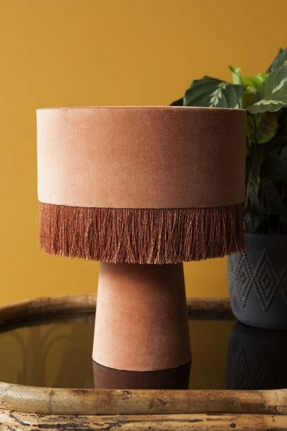 lifestyle image of All Over Velvet Table Lamp With Fringe - Dusky Rose with plant in vase on black table and french ochre painted wall background