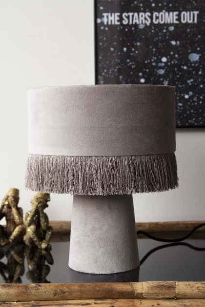 lifestyle image of All Over Velvet Table Lamp With Fringe - Ice Grey with black art print and Three Wise Monkey Ornaments - Antique Bronze on black console table and pale grey wall background