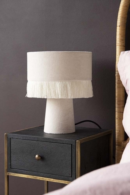 Lifestyle image of the All Over Velvet Table Lamp With Fringe - Snow White on black bedside table with dark wall background