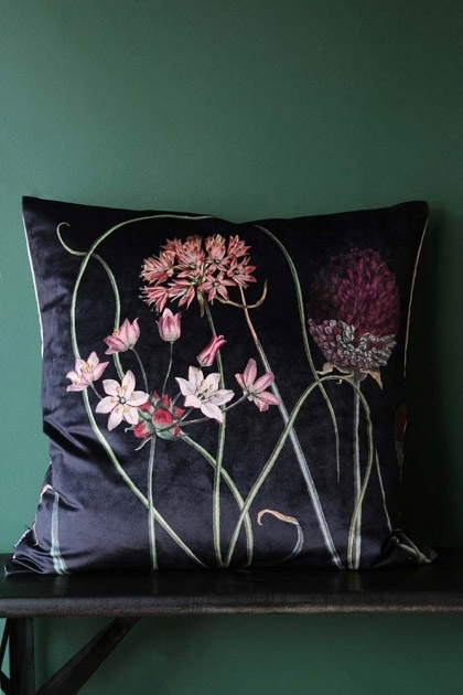lifestyle image of Allium Velvet Cushion - Black on black table and dark green wall background