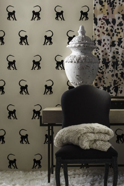 lifestyle image of Andrew Martin Cheeky Monkey Wallpaper - 3 Colours Available with black chair and grey blanket on top in front of desk with large white vase