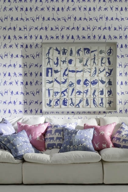 lifestyle image of Andrew Martin Mischief Wallpaper - 4 Colours Available with blue and white art on wall and cream sofa with pink and blue cushions