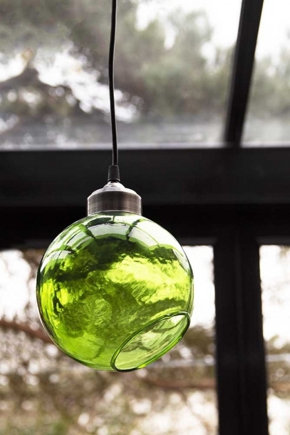 Lifestyle of angled glass sphere pendant ceiling light in green with window background