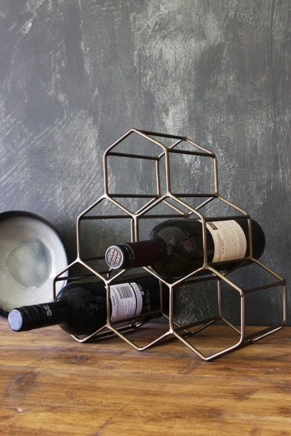lifestyle image of Antique Brass Geo Wine Rack with bottles inside on wooden table and distressed grey wall background
