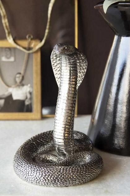 lifestyle image of Antique Silver Cobra Snake Ornament on marble table with black terracotta vase and picture frame in background with dark wall