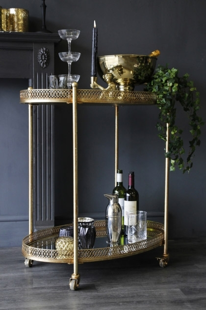 lifestyle image of Antique Style Gold Metal Drinks Trolley filled with drinks and ornaments with grey wall background