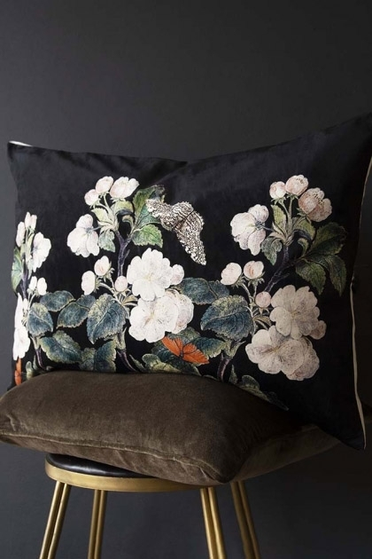 Lifestyle image of the apple blossom floral butterfly velvet cushion in black on a stool with dark wall background