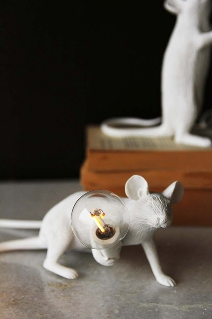 lifestyle image of Aramis The Crouching Mouseketeer Lamp - White lit up on marble surface with pile of books and second mouse lamp in background