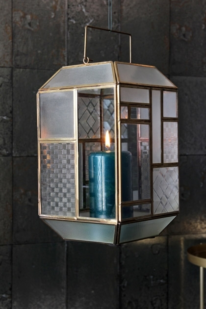 lifestyle image of Art Deco Brass & Glass Lantern with blue lit candle inside with grey tiled wallpaper background