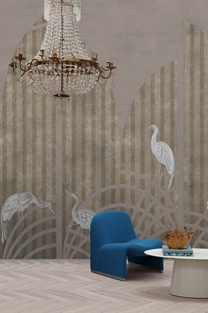Lifestyle image of the Art Deco Wallpaper Mural - Tassel Rose Pink with blue armchair and white coffee table and large gold and glass chandelier hanging from ceiling and pale parquet flooring