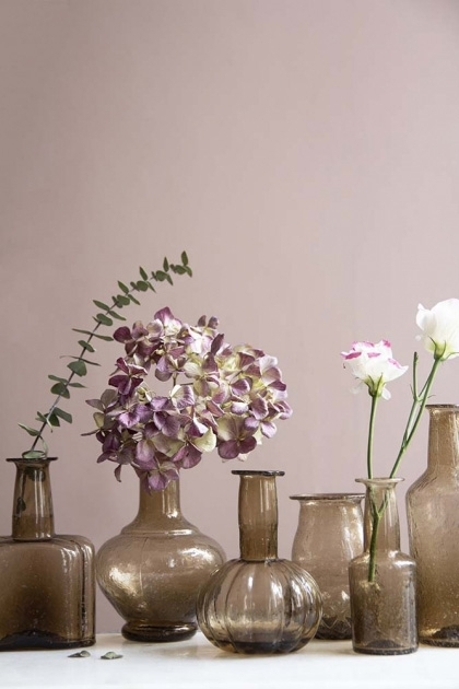 Lifestyle image of all of the recycled glass vases with flowers inside and pale pink wall background