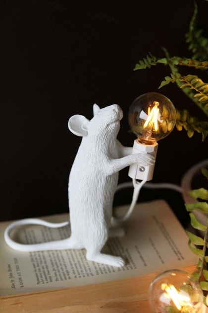 lifestyle image of Athos The Standing Mouseketeer Lamp - White lit up on open book with house plant and dark wall background