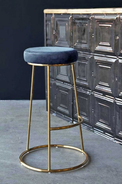 Lifestyle image of the Atlantis Bar Stool in Petrol Blue next to tin tile wall and on grey flooring with dark blue painted wall background