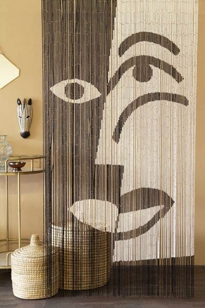 Lifestyle image of the Black & White Design Bamboo Door Curtain with Moroccan basket and gold side table with cloisters painted wall background