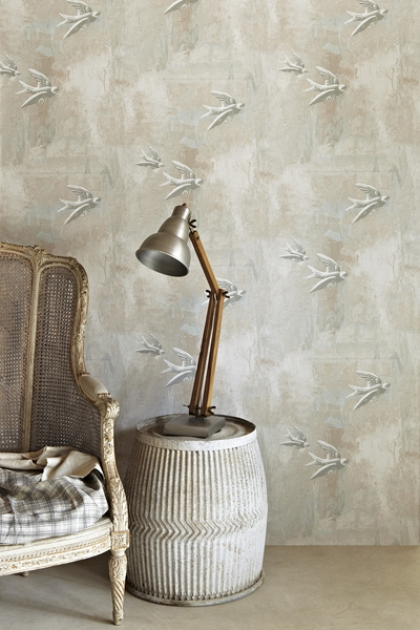 lifestyle image of Barneby Gates Fresco Birds Wallpaper with distressed armchair and wooden side table with table lamp in front