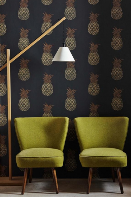 lifestyle image of Barneby Gates Pineapple Wallpaper - Charcoal with two green armchairs and floor lamp with white shade