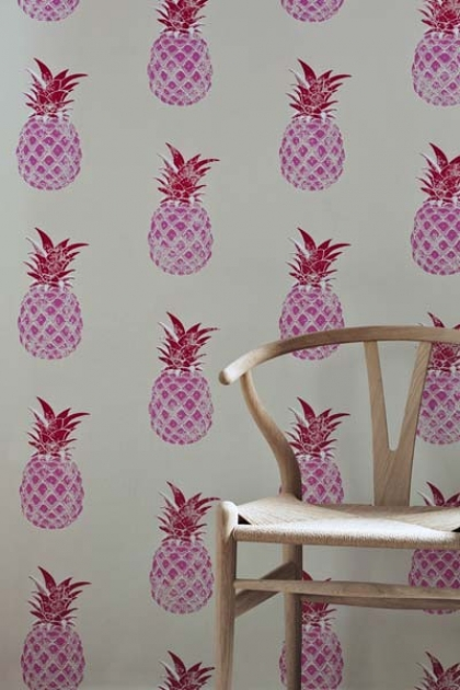 lifestyle image of Barneby Gates Pineapple Wallpaper - Pink/Red with wooden chair in front