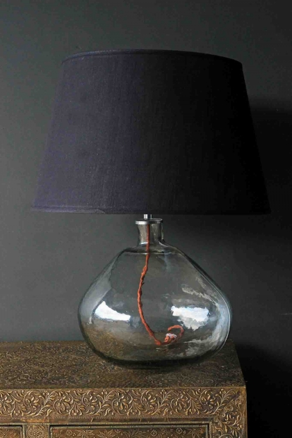 Beautiful Glass Table Lamp Base on wooden table with dark wall background and blue lamp shade lifestyle image