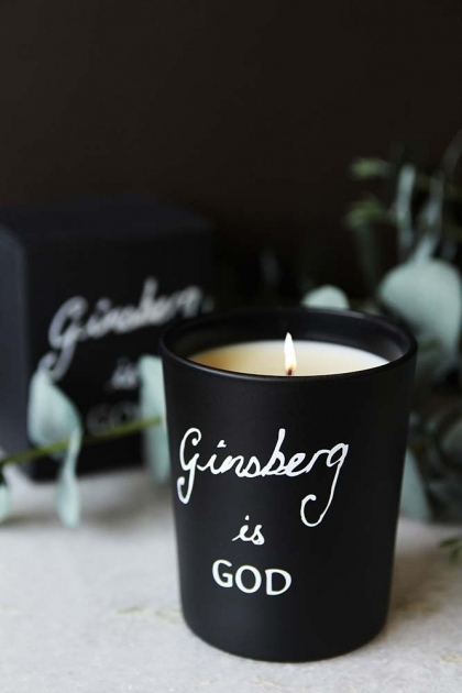 lifestyle image of Bella Freud Ginsberg Is God Candle on marble counter with eucalyptus and box in background and dark wall background