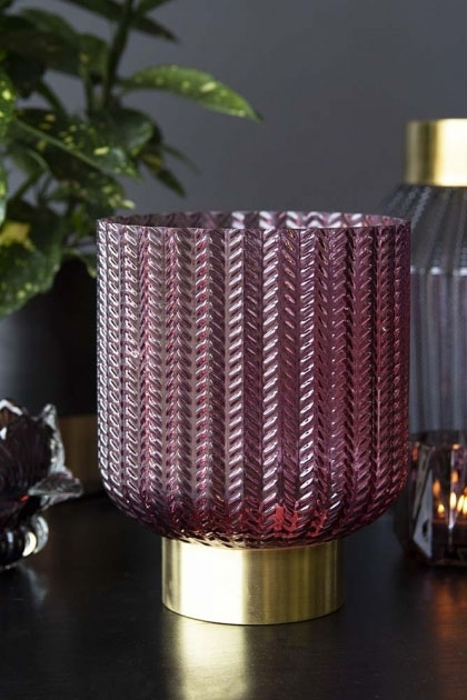 lifestyle image of Berry Tinted Glass & Gold Chevron Vase with other glass vase and plant on black table and dark wall background