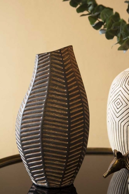 Lifestyle image of the Black African Ceramic Chevron Vase on black side table with vase and eucalyptus in background with closters painted wall background