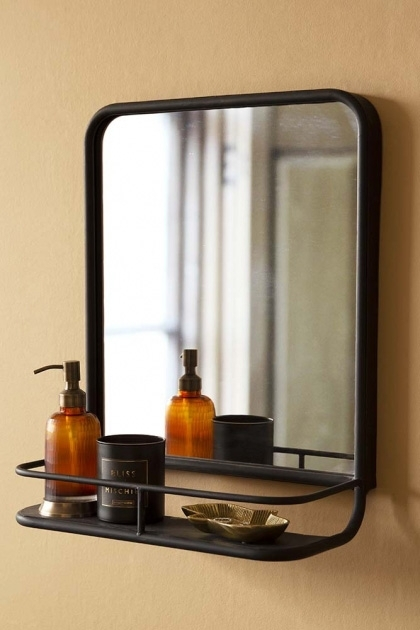 Lifestyle image of the Black Square Bathroom Mirror With Shelf hung on the wall with bathroom accessories on shelf with pale wall background