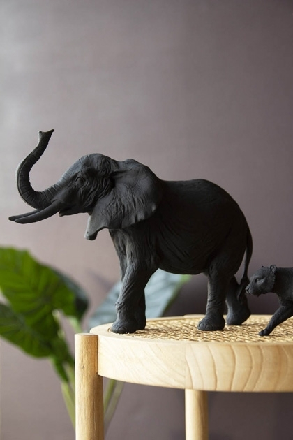 Lifestyle image of the Black Bull Elephant Ornament on wooden side table and house plant in background with dark wall background