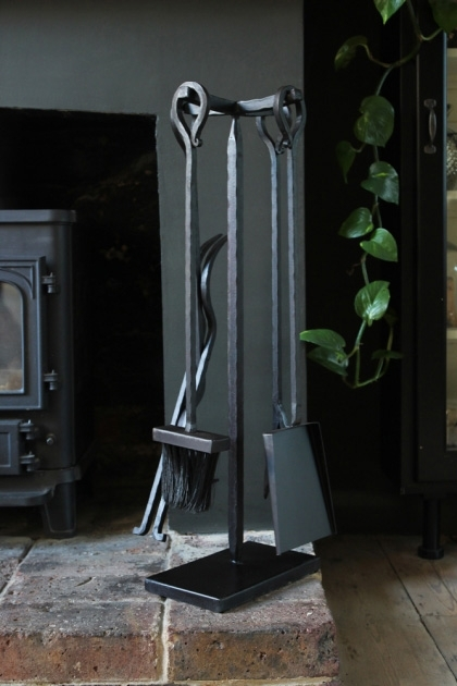 lifestyle image of Black Fireside Tool Set next to fireplace on dark wooden floor and plant in background
