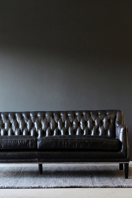 Lifestyle image of Black Leather Chesterfield 3 Seater Sofa on grey rug and dark wall background