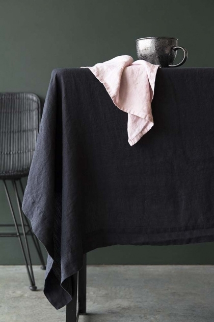 lifestyle image of Black Linen Tablecloth on dining table with mug on top and black rattan dining chair with grey flooring and dark green wall background