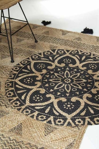 lifestyle image of Black Mandala Pattern Natural Jute Circular Rug on top of Natural Jute Rug With Black Tassels with dining chair in background