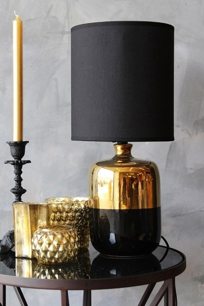 lifestyle image of Black & Bronze Table Lamp on black tray side table with gold vases and black candle holder with gold candle in and grey wall background