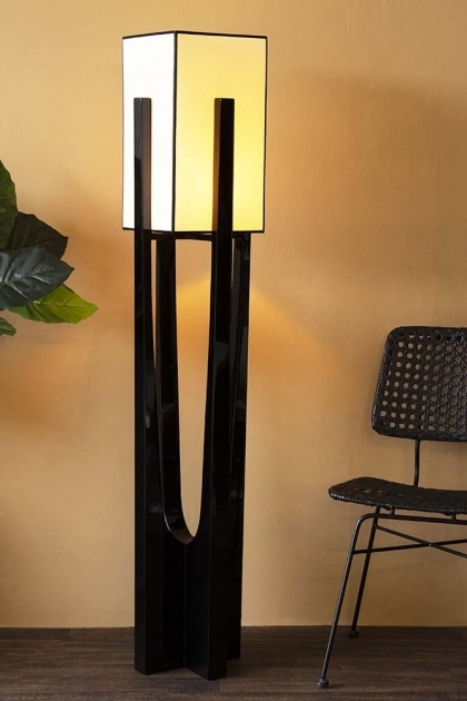 Lifestyle image of the Black & White Art Deco Design Floor Lamp lit up with black rattan chair and house plant in background and cloisters painted wall background