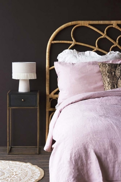 Lifestyle image of the Bloom Natural Rattan Headboard - Double Bed with Black Wood and Brass Leg Bedside Table and pink bedding, pink velvet lamp and jute rug with dark wall background