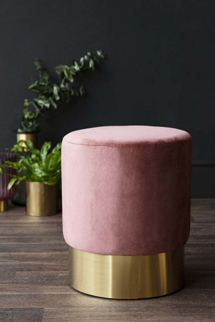 lifestyle image of Blush Pink Velvet Pouffe Stool With Gold Base - Small with plants in gold pots in background on wooden flooring and dark wall background