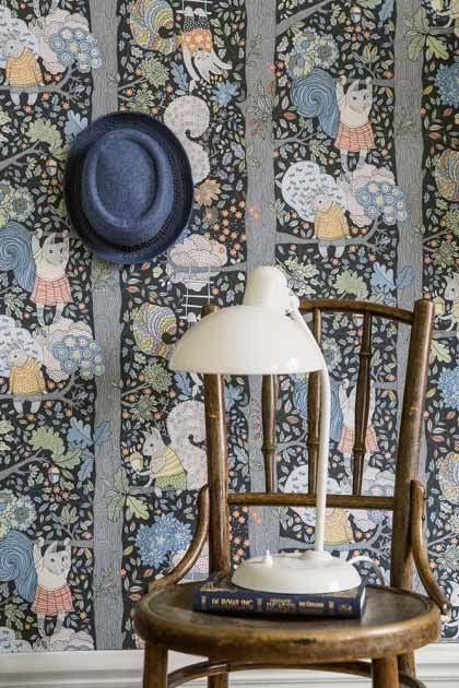 lifestyle image of BorasTapeter Scandinavian Designers Mini Collection Wallpaper - Charlie - 2 Colours Available wooden chair with white table lamp and blue hat hanging on wall