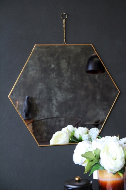 lifestyle image of Brass Framed Hexagonal Mirror with white flowers in front and hung on dark wall background