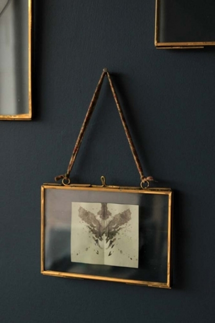 4x6 brass and glass landscape picture frame with a rorschach test image inside on dark wall on own lifestyle image