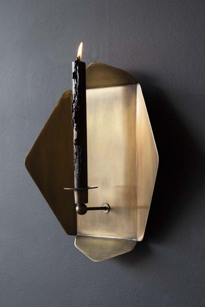 lifestyle image of Brass Octagon Wall Sconce with tall black candle lit inside hung on dark grey wall background