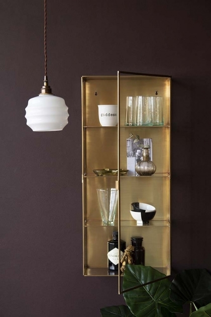Lifestyle image of the Brass & Glass Wall-Mounted Display Cabinet with pendant light and house plant on dark wall background