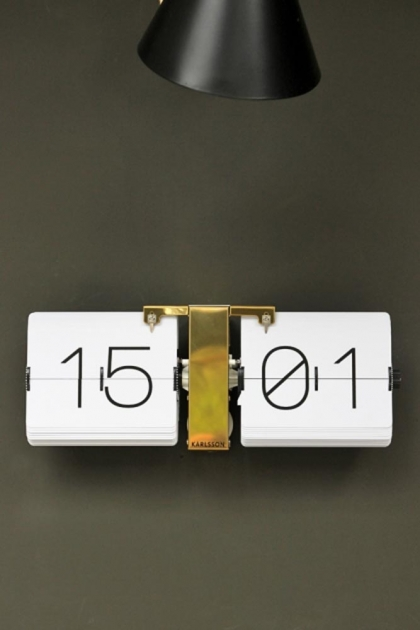 White flip clock with brass stand featured under a black lampshade