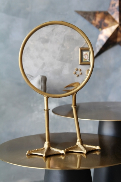 lifestyle image of Bronze Bird Feet TableVanity Mirror on gold side table and copper star hung on distressed grey wall background