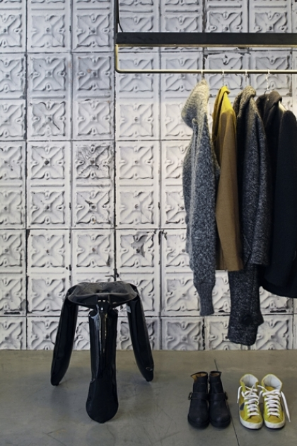 Lifestyle image of NLXL TIN-04 Brooklyn Tin Tiles Wallpaper By Merci with dark blue stool and clothing rack with clothes hanging from it and shoes on the floor