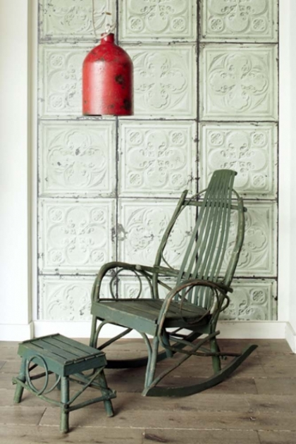 Room with a weather dark green rocking chair, red shaded ceiling pendant featuring green tin tiles wallpaper.