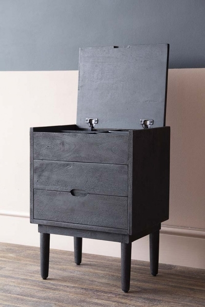 lifestyle image of Bureau-Style Black Mango Wood Bedside Table with lid open on wooden flooring and contrasting wall background