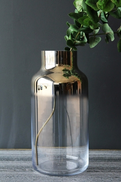 lifestyle image of Cabrillo Gold Top Vase with plant in on grey table and dark wall background