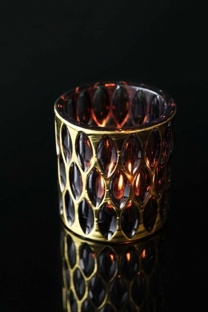 lifestyle image of Calisson Tea Light Holder with lit tea light inside on black table background