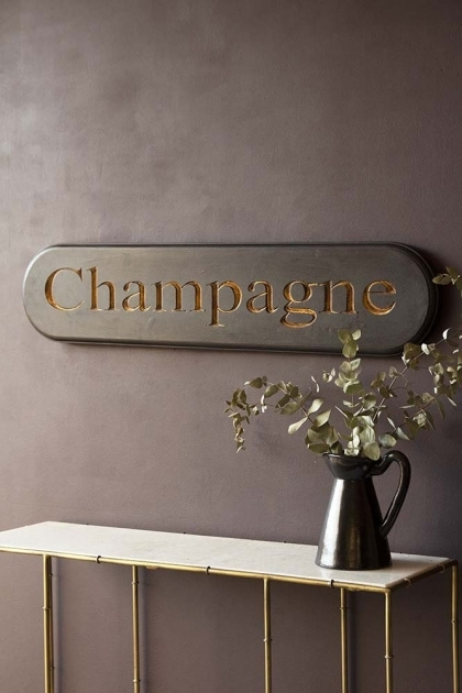 Lifestyle image of the Carved Champagne Sign over marble console table with vase on top and dark wall background